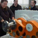 Studentin bewegt einen Unwuchterreger für eine Schwingsiebmaschine von Haver Niagara