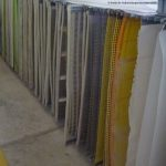 Different types of screen coverings hung up in a row, used by Haver Niagara for various applications