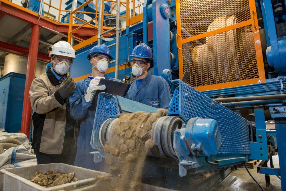 Das Bild zeigt einen Mitarbeiter der Maschinenfabrik Köppern GmbH & Co.KG und zwei Studenten, die den Brikettiervorgang an einer Walzenpresse verfolgen.