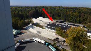 Blick vom Siebturm auf wartende LKW und den Radlader, der Material von der Reservehalde zulädt.