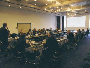 Besprechungsraum mit ca. 50 Teilnehmern - ein Teilnehmer steht und hält ein Mikrofon