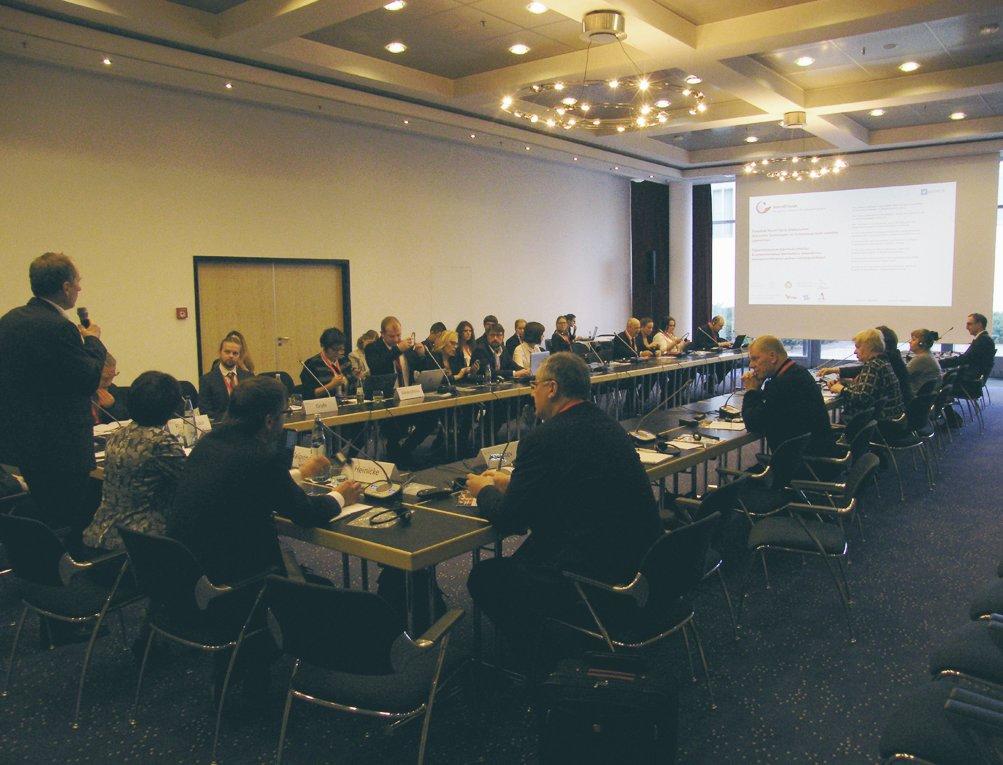 Das Bild zeigt ein Bsprechungsraum mit ca. 50 Teilnehmern . EIn Teilnehmer steht und hält ein Mikrofon