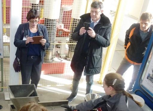 Die Kolloquiumsteilnehmer führen im Technikum des Instituts für Aufbereitungsmaschinen Versuche an einer Gutbett-Walzenmühle durch