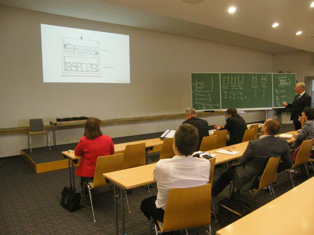Das Bild zeigt Prof. Unland beim Vortrag zu Grundlagen der Gutbettzerkleinerung sowie weitere Teilnehmer, die seinen Ausführungen aufmerksam folgen