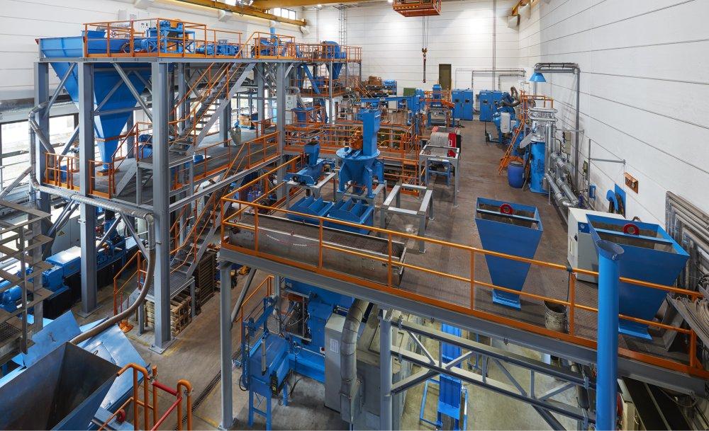 Das Bild zeigt eine große Versuchshalle mit Walzenpressen in kleiner Industriegröße am Institut für AUfbereitungsmaschinen der TU Bergakademie Freiberg