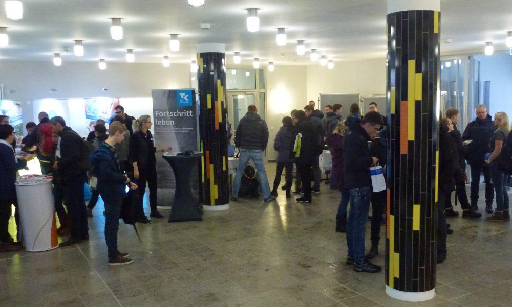 """Foyer vom Weisbachbau mit vielen jungen Besuchern und einem Poster """"Fortschritt erleben"""""""