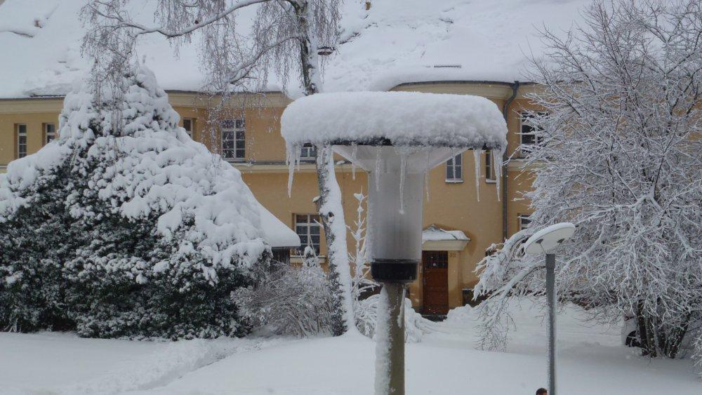 das Bild zeigt eine verschneite Laterne mit Eiszapfen vor einem verschneiten Gebäude