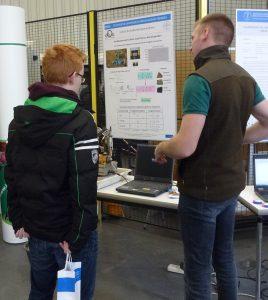 Ein Assistent vom IAM erläutert einem Besucher die Funktion eines PLT-Gerätes