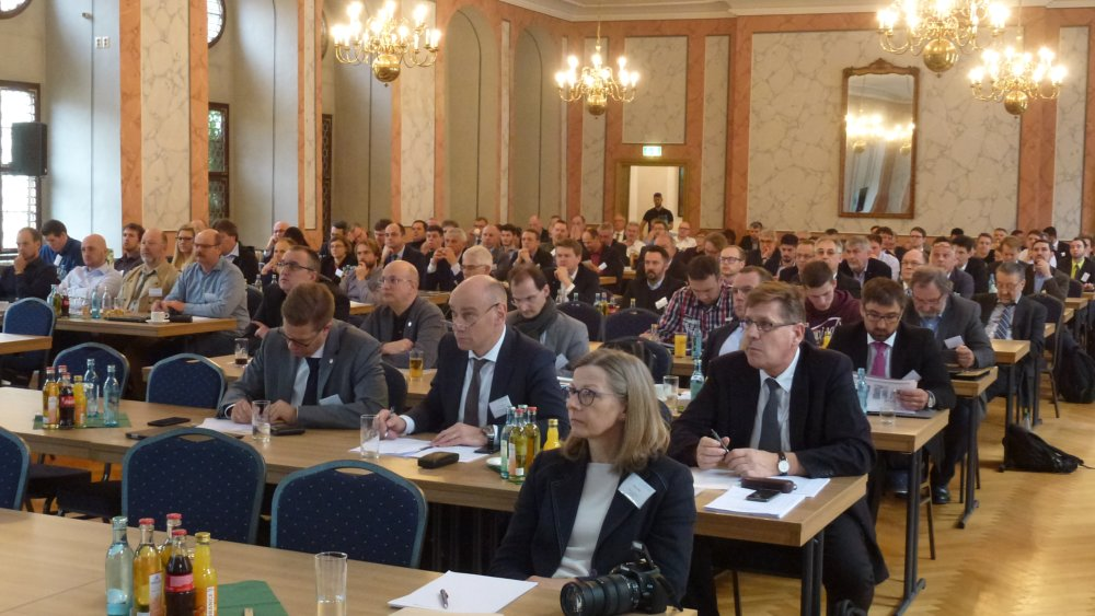 The picture shows about 140 people in business dresses following a presentation inside the Municipal Ceremonial Hall of Freiberg
