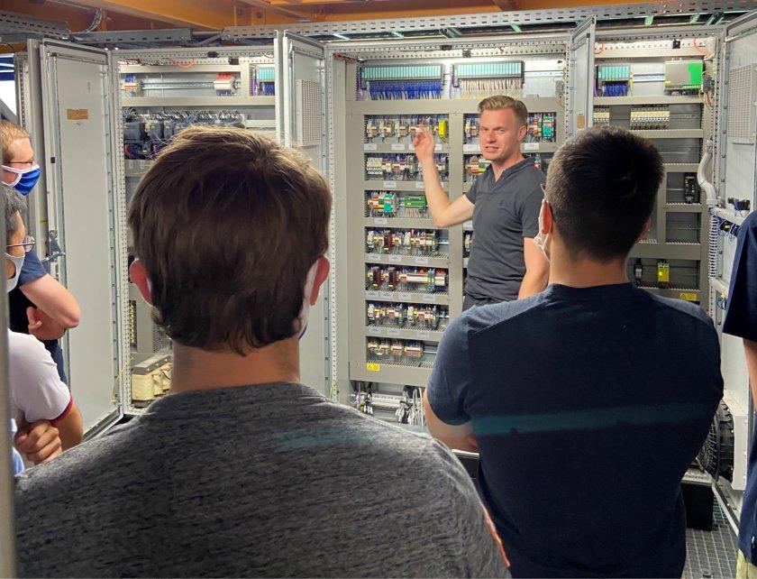 Ein Mitarbeiter vom IAM erläutert Studierenden den Signalfluss am geöffneten Schaltschrank einer Mahlanlage im IAM