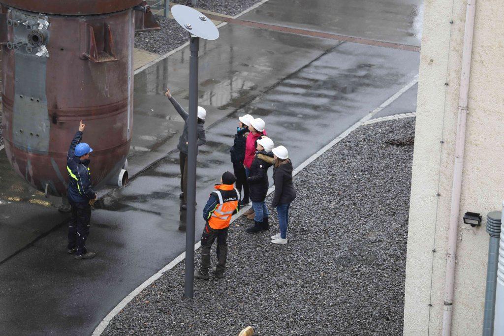 Schülerinnen stehen vor Reaktor und diskutieren mit Anlagenpersonal über Funktionsweise des Behälters