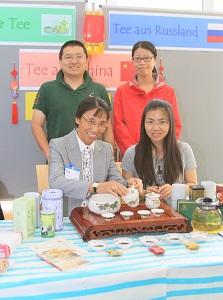 Chinesen an einem Tisch bieten Tee an