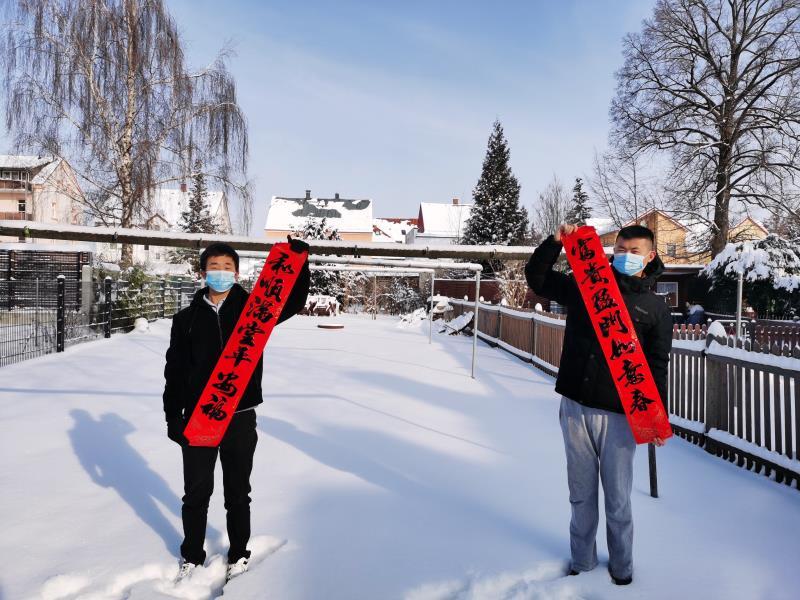 Zwei chinesische Studenten grüßen mit Schriftbannern zum Neujahrsfest