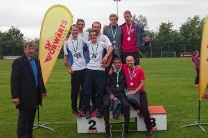 Die Staffel-Teilnehmer der TU Freiberg und der Uni Leipzig stehen auf dem Sieger-Treppchen und lachen in die Kamera